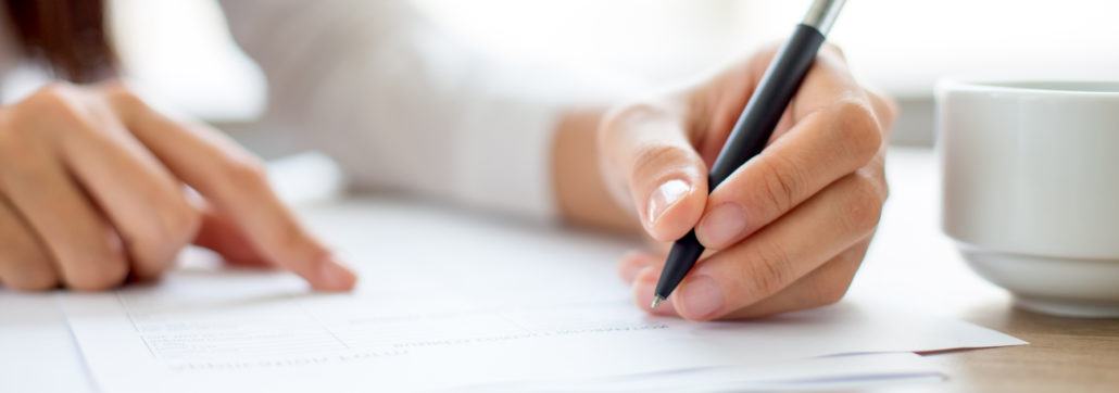 Hand of young businesswoman writing on paper or signing contract at table in office