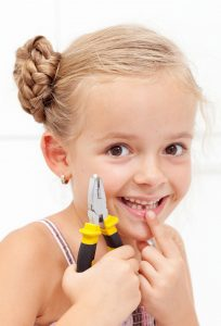Little girl smiling, holding her missing tooth with pliers showing the gap